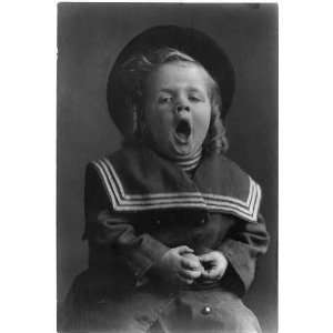 boy with long hair wearing hat,sailor coat yawning,c1909,curly hair